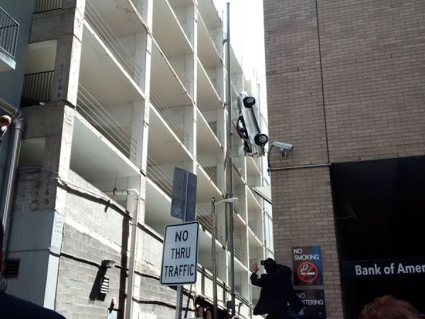 Vehicle dangling from parking garage in downtown Austin